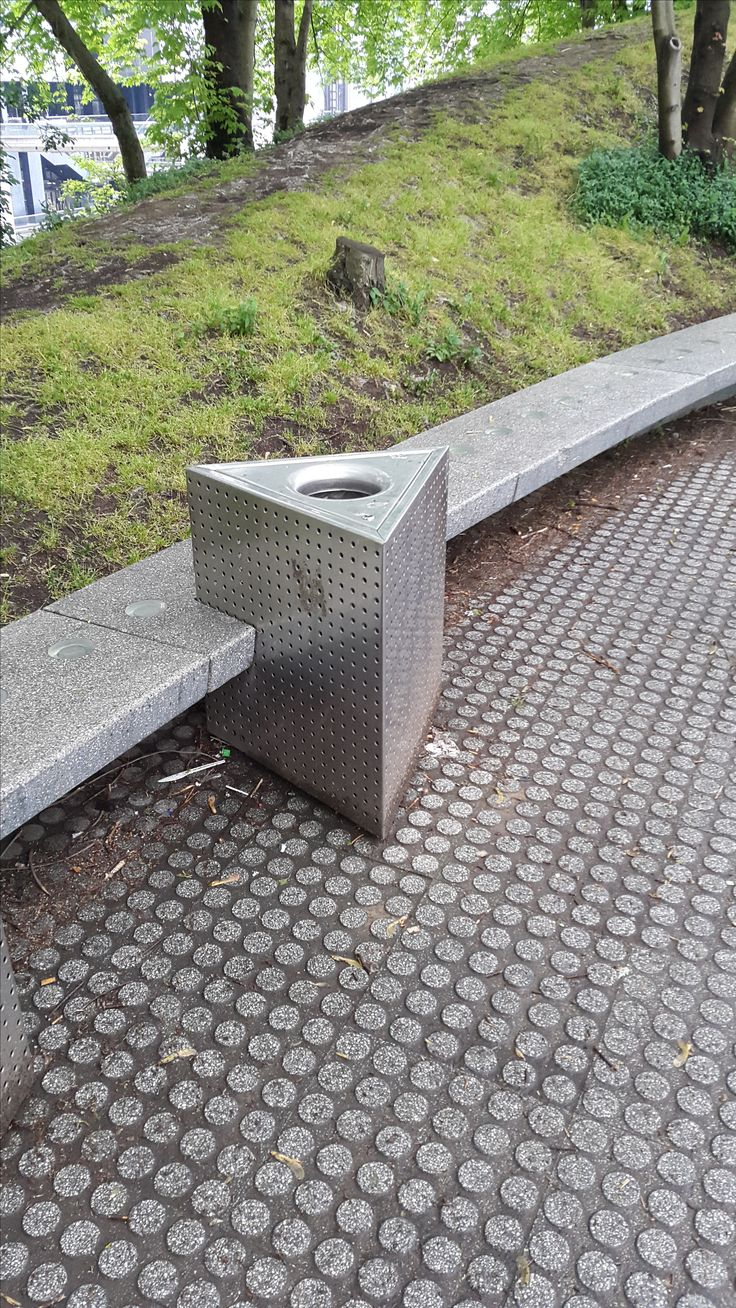 Metalen driehoekige afvalbak bevestigt in betonnen bank, Parc de la villette