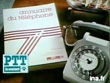 Annuaire papier et téléphone gris à cadran.
