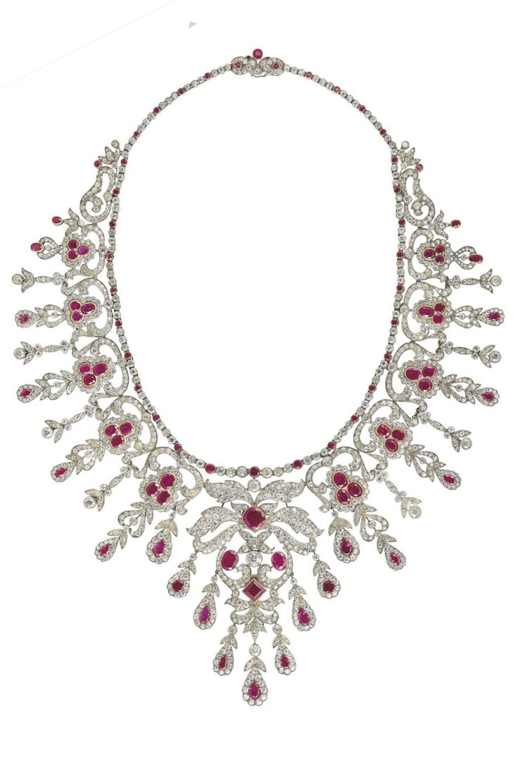 A BELLE EPOQUE RUBY, SYNTHETIC RUBY AND DIAMOND FRINGE NECKLACE, CIRCA 1910. Of openwork scrolling design, set throughout with old-cut diamonds and variously-cut rubies and synthetic rubies, mounted in silver and gold.