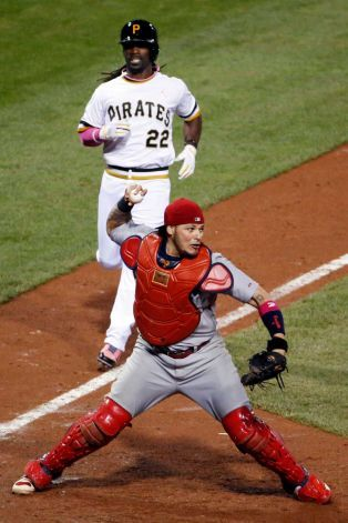 St. Louis Cardinals catcher Yadier Molina throws to first to complete a game-ending double play on Pittsburgh Pirates' Jordy Mercer at first base, after getting the force out at home on Pirates' Andrew McCutchen (22) during the ninth inning of a baseball game in Pittsburgh, Sunday, May 11, 2014. The Cardinals won 6-5. Photo: Gene Puskar, AP / AP