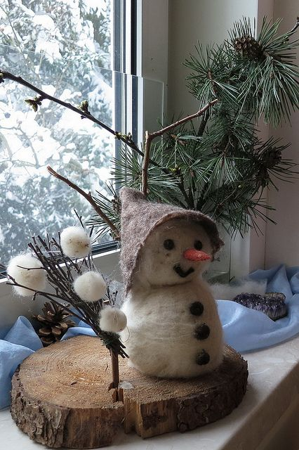 Sooo cute and sooo original to prim up a window sill!  Love the details... his hat, the arsenal of snowballs, the tree slab riser, etc!