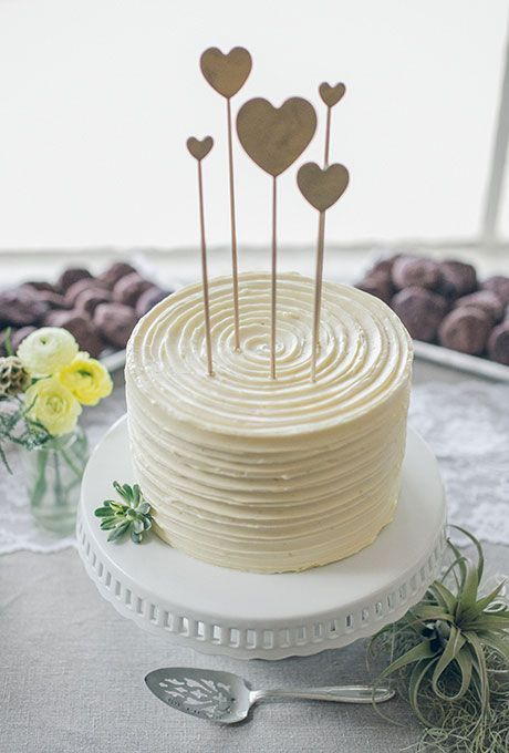 A simple one-tier white wedding cake with heart toppers | http://Brides.com