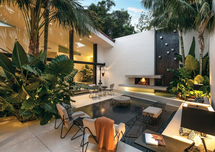 obsessed with the mix of modern + natural elements in this backyard oasis - the foliage, the mod furniture + the luxe outdoor fireplace