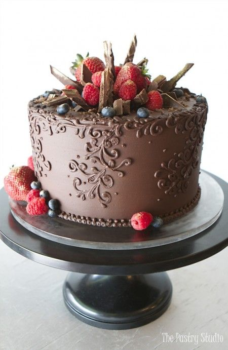 rich chocolate single tier cake with ornate scrolling and gold brushed berries and chocolate shards