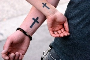 a young christian couple show their matching cross tattoos. the crucifix designs are poignantly placed - on the wrists where nails would have been driven through jesus's wrists during the crucifixion.
