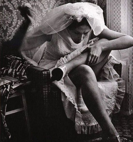 A bride mending her stocking before registration 1970s