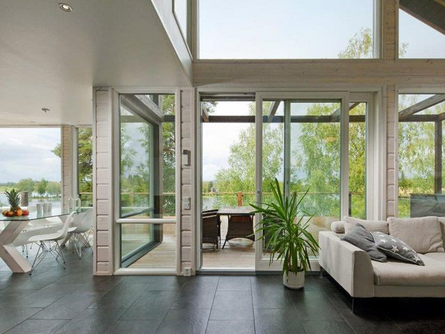 Large windows with a sliding door to the terrace gives a large view for the lake and natural garden. Black floor tiles gives a nice contrast to the white lacquered pine lg walls. Interior architect Hanna-Marie Naukkarinen and architect Jussi Hietalahti.