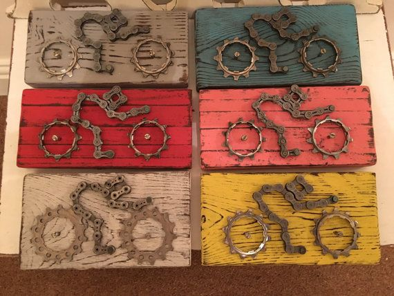 These hand made cycling wall plaques feature a cyclist / time trialist / triathlete and have been made by me from recycled bicycle parts and recycled pallet wood. The plaques are made from recycled bicycle chain, bicycle gears and wheel spokes mounted on recycled pallet wood. Each one is approx 18cm long x 9cm wide x 2.5cm deep.  The plaques are available in a variety of finishes including the following stock finishes: Natural Brown Wood or Light Pine Wood Chalk Painted and distress...