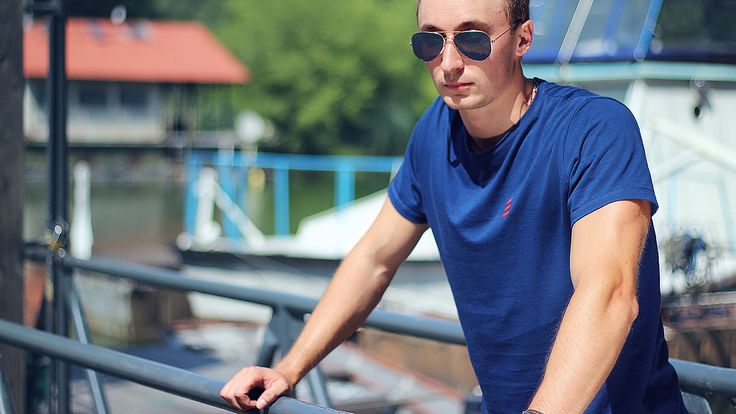 Man in harbor. Model wears Navy Explore T-Shirt by Pharos Apparel and Aviator sunglasses