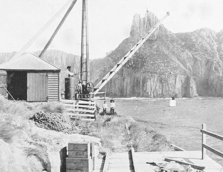 Tasman Island Steam Winch unloading passengers from boat below cliff, unknown date.