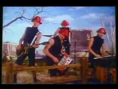 Devo - Whip It (1980).  Band paid $15k of their own money to make this video.  This song was Devo biggest hit and Energy Dome gear hats and black wife beaters were born.   The band got into alot of trouble with S & M theme of this video.