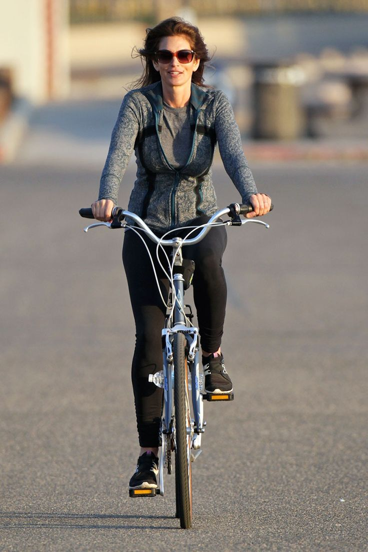 Cindy Crawford makes activewear look chic on a late-afternoon bike ride.   - HarpersBAZAAR.com