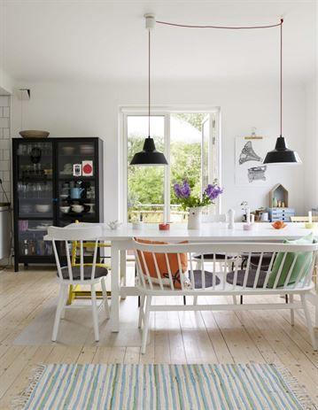 Matrummet är inrett med ljus bar där färgglada accessoarer sätter stilen. Taklampor från Fform. Bord och vitrinskåp från Ikea.
