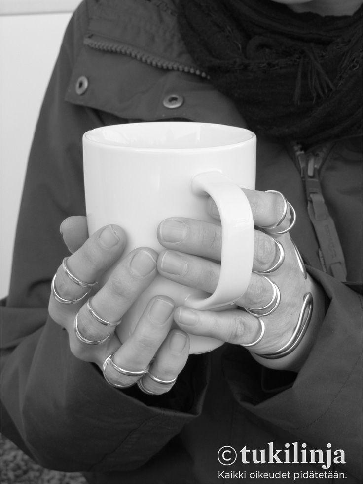 """8. Ronja Venesperä: KAHVILLA  -   """"Kuvassa näkyvät """"sormukset"""" ovat sormiortooseja, jotka estävät hypermobiileja sorminiveliä menemästä sijoiltaan. Ortoosit mahdollistavat normaalin käsien käytön, kuten teen juomisen kahvilassa."""""""