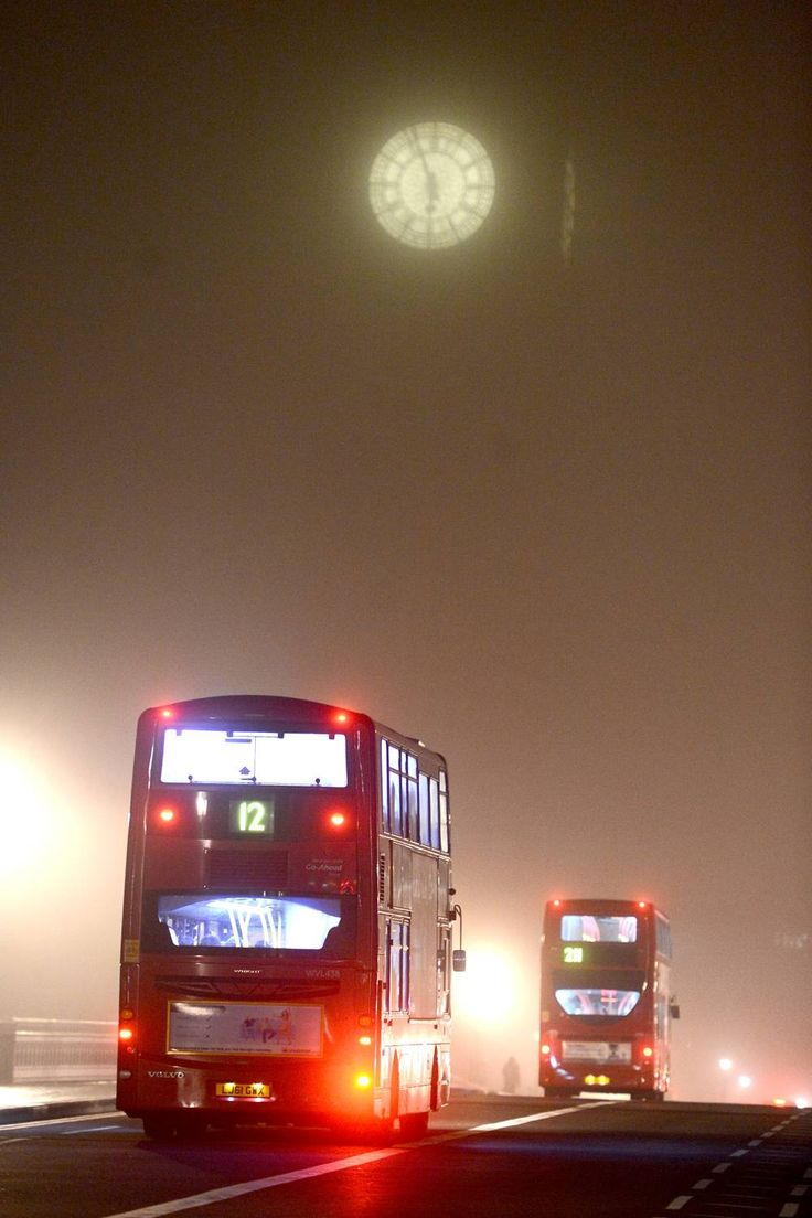 London fog: buses make their way through the misty conditions on Westminster Bridge