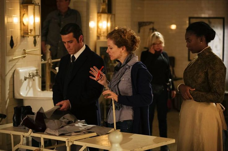 "Yannick Bisson (""Murdoch""), director Leslie Hope and Mouna Traoré (""Rebecca James"") discuss the next scene in the morgue set"