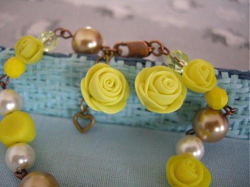 Set ručne robeného náramku a náušníč s ružami vo vintage štýle. Ruže sú modelované z polymérnej hmoty citrónovo žltej farby. Náramok je kombinovaný s maslovo bielymi a béžovými voskovanými perlami, ružami a žltými brúsenými ohňovkami. Náušničky sú zapichovacie, so silikónovými zarážkami. Komponenty sú kombinované vo farbe staromeď a staromosadz