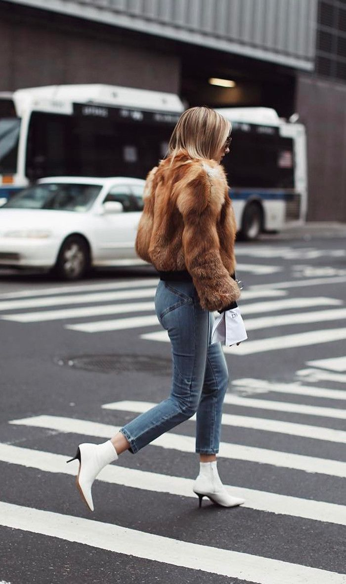 WeWoreWhat wearing a fur coat, denim jeans and white boots
