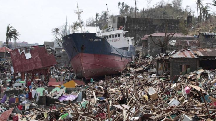 In Philippines, battered town stops waiting for help, gets busy rebuilding - Air crew onboard a U.S. Navy helicopter attached to the aircraft carrier USS George Washington carry out a search Friday north of typhoon-ravaged Tacloban, Philippines