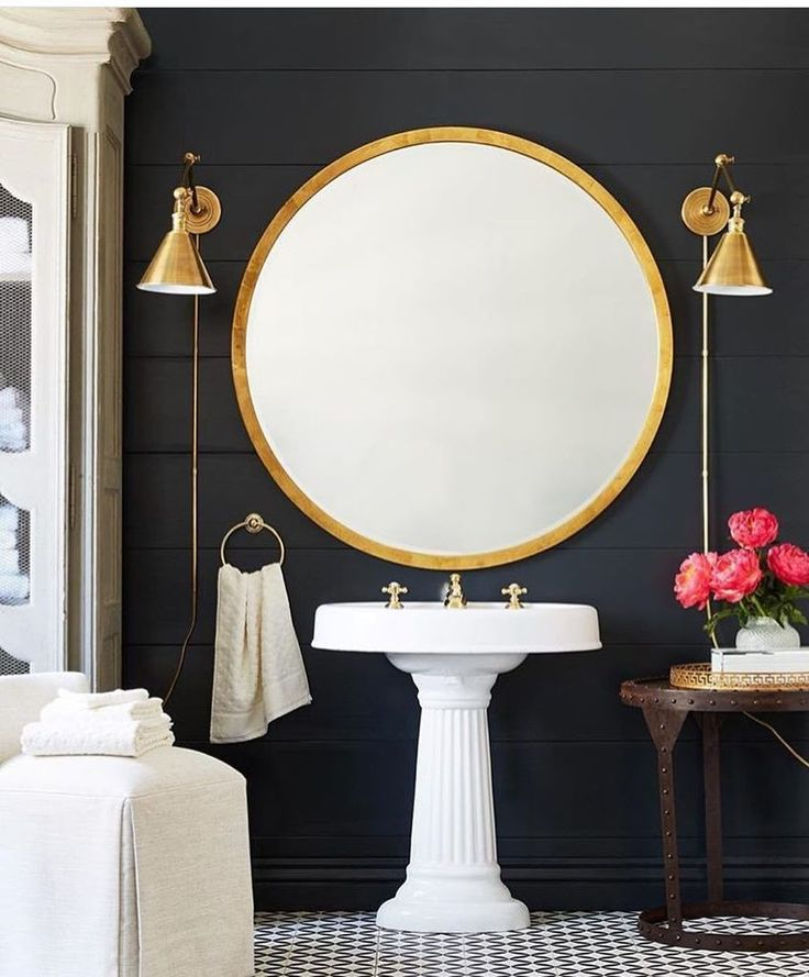 Gorgeous gold round mirror and brass wall sconces in this modern-meets-classic master bathroom!