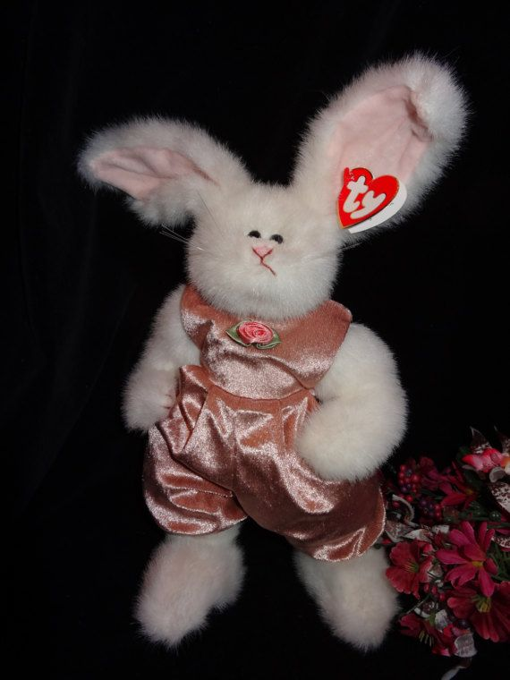 Sara Bunny is ready for Easter! Spring is in the Air!! As it says on her paper heart tag. She was made by the TY Company, and is part of the Attic Treasures Collection. She was first produced in 1993. She is in perfect condition, never played with. She is white faux fur and wears a soft light mauve velveteen jump suit. Sara is 11 inches tall not including her ears. She is fully jointed and can pose. She would make a wonderful decoration for Easter and Spring!  Thanks for looking! Please…