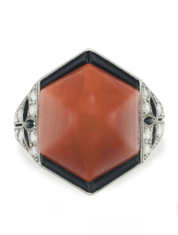 AN ART DECO CORAL, ONYX AND DIAMOND RING, CIRCA 1930. Set with a hexagonal-shaped sugarloaf cabochon coral, within a sculpted black onyx surround, to the old-cut diamond and navette-shaped onyx shoulders, mounted in platinum.