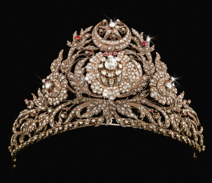 A RARE OTTOMAN DIAMOND AND RUBY SET GOLD TIARA, TURKEY, CIRCA 1800 the foliate openwork frame supporting attached elements set with cut-diamonds, the centre with a large diamond floral rosette radiating diamond-set petals issuing floral sprays set with diamonds and rubies, the crown with a star and crescent motif, suspension loops to the sides