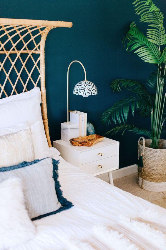 Un bleu pétrole et des accessoires naturel: tête de lit en bois tissé, panier en osier pour une ambiance jungle