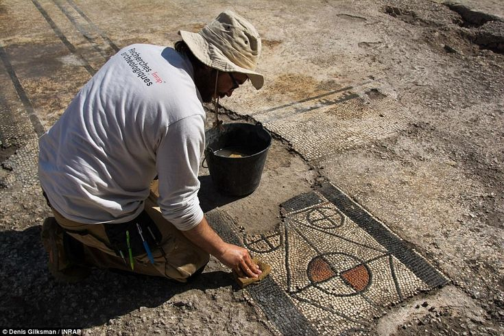A researcher scrubs dirt away from part of the intricate mosaic. Researchers have suggested the floor may have been part of an elaborate reception room.