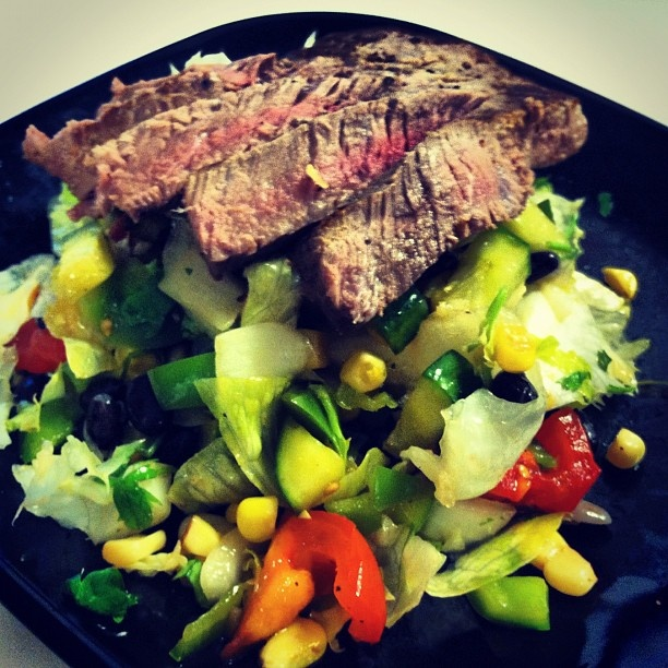 Lean cut London Broil over a bean and veggie salad with a cilantro lime dressing. Follow my instagram for more low cal meal ideas! @robolikes