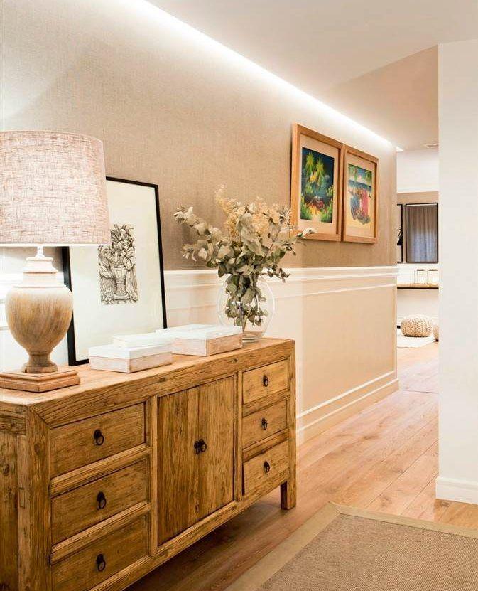 Recibidor con cómoda de madera envejecida, tiradores de metal, luces empotradas, arrimadero blanco y cuadros