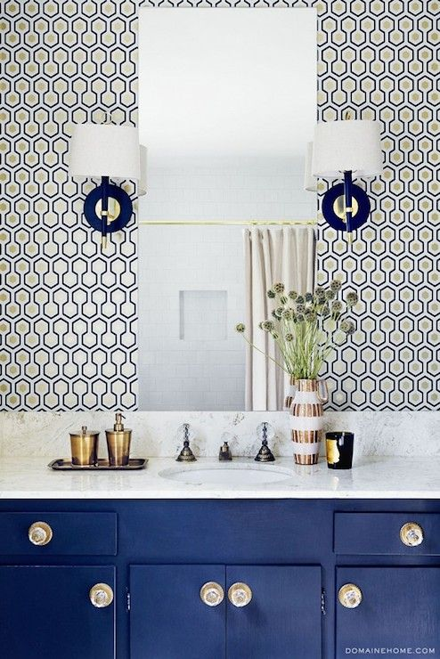 The Kitchy Kitchen - Fabulous bathroom features blue vanity topped with white countertop situated under frameless mirror mounted on David Hicks Hex Wallpaper illuminated by Jonathan Adler Ventana Wall Sconces.