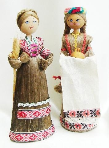 """BELARUS - Festival doll and Welcoming doll Belarus was formerly known as the Soviet Republic of Belorussia. Wooden dolls with knob heads, padded stick bodies and painted features. They both have skirts made of fibre. The doll on the left is a Festival doll holding a sheath of barley. The doll on the right is a """"Welcoming"""" doll, the tradition being to give the guests salted bread. This doll has two plaits down to her knees. 2006."""