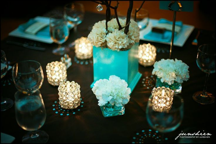 Light aqua or Tiffany blue centerpiece with white carnations, candles, and branches with what looks like some kind of bling maybe?  Nifty!