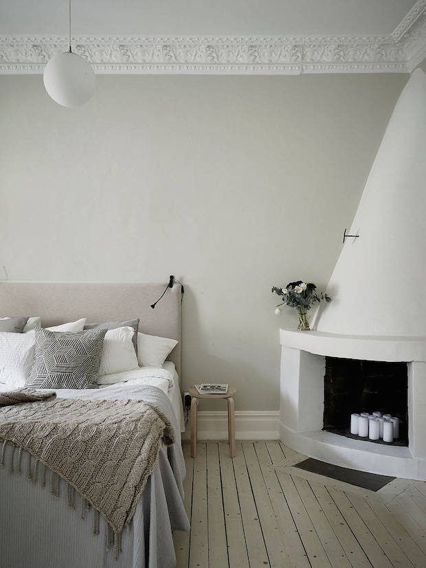 Bedroom with a lovely white fireplace in a calm Swedish home. Stadshem.