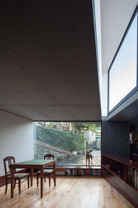 A triangular lightwell covered in scale-like shingles extends from the roof of this living room that architect Nuno Melo Sousa has added to a house in Penafiel, Portugal.