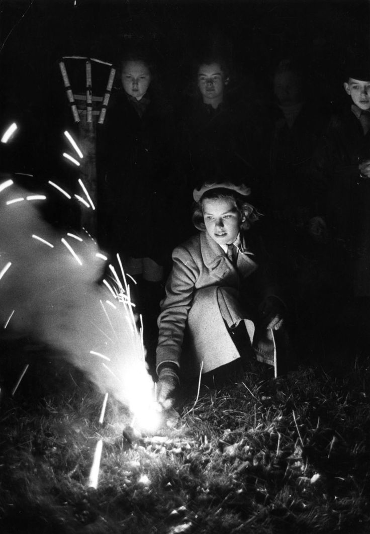 Charles Hewitt - Lighting A Firework. A girl lights a firework at a Guy Fawkes night party, 1952. °