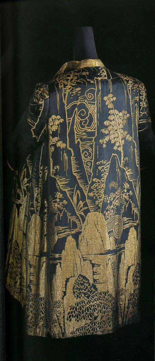 Манто. Около 1923 или 1960-е, Франция. Черная и золотистая шелковая атласная парча, большой узор-пейзаж, подобранный при раскрое ткани, воротник из золотистой ткани ламе, такие же манжеты и подкладка, низ с подбивкой, длина по колено.