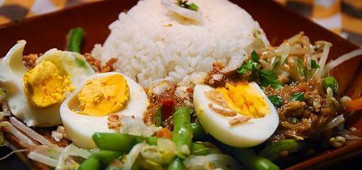 Een lekkere en gezonde vegetarische maaltijd. Witte rijst met geblancheerde sperziebonen, taugé en gekookte eieren met satésaus, gebakken uitjes en kroepoek.