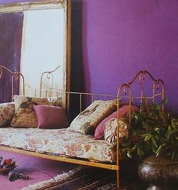 Lit en fer ancien revisité en banquette avec ses coussins fleuris et colorés