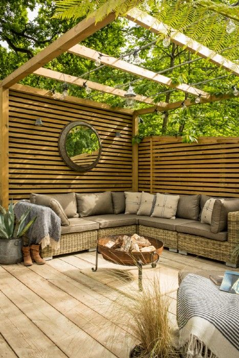 Large decking area with a festoon lit pergola area and rattan corner sofa