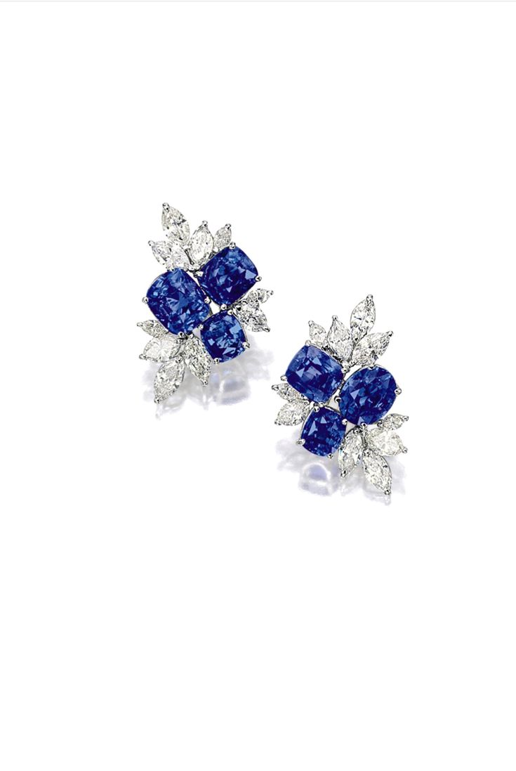 Pair of Sapphire and Diamond Ear Clips. Of cluster design, each set with an oval and two cushion-shaped sapphires, decorated by marquise-shaped diamonds, the sapphires and diamonds altogether weighing 19.55 and 6.40 carats respectively, mounted in platinum, with clip and post fittings.