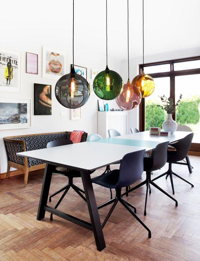 Salle à manger avec une grande table blanche et suspensions déco