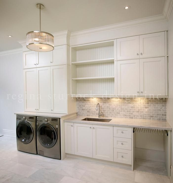 Upstairs laundry room features front-load washer and dryer under stacked cabinets atop white marble staggered floor.