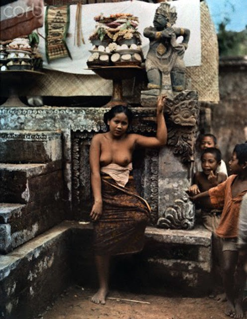 ca. November 1937, Bali, Indonesia --- A woman leans against a stone platform where offerings are made --- Image by © Maynard Owen Williams/National Geographic Society/Corbis