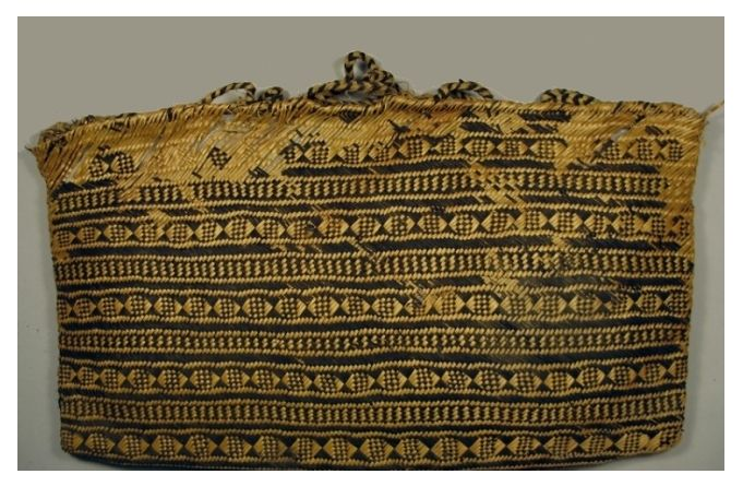 Kete, (Maori woven basket) made out of black and natural coloured harakeke (flax), with ten small looped handles made out of plaited black and natural coloured muka fibre (flax fibre) along the top, five on each side.