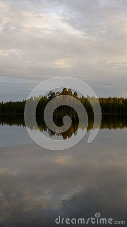 Picturescue of a iland in a glassy lake, nordic climate, summertime.