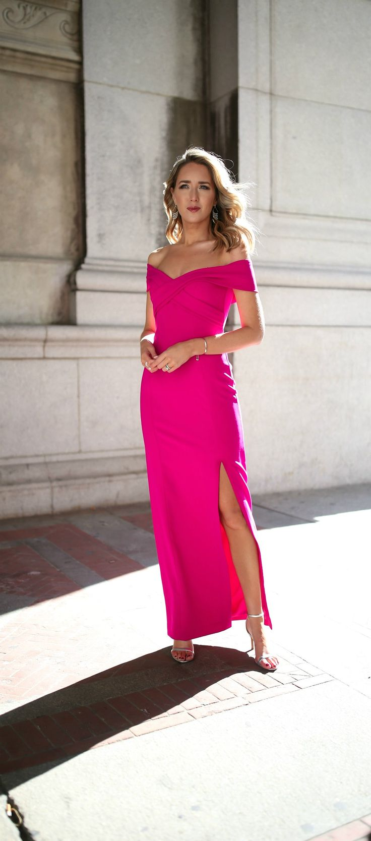 What to Wear to a Black Tie Wedding // floor length fuschia pink formal gown with off the shoulder v-neck neckline and criss cross front, classic fitted sheath silhouette, slit up leg, simple silver metallic ankle strap mid-heel sandals