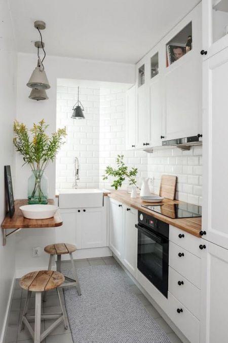 Mała kuchnia zaaranżowana w skandynawskim stylu, w całości w białym kolorze. Drewniane blaty i niektóre dodatki urozmaicają jasną przestrzeń i dodają jej przytulności. Świeże kwiaty na podobnej zasadzie dekorują przestrzeń.