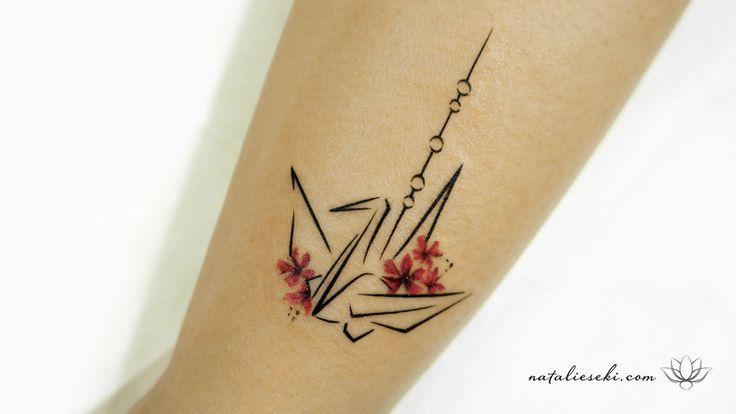 Tatuagem delicada de origami de tsuru – a garça, uma ave sagrada para os japoneses – no tornozelo da Larissa.